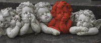 Four carved white stone cherubs, one red